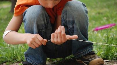 un enfant joue avec une ficelle