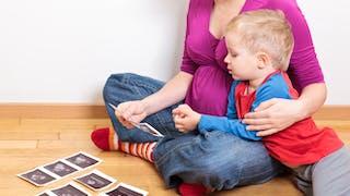 femme enceinte montre échographie à son enfant