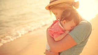 bébé à la plage dans les bras de sa mère