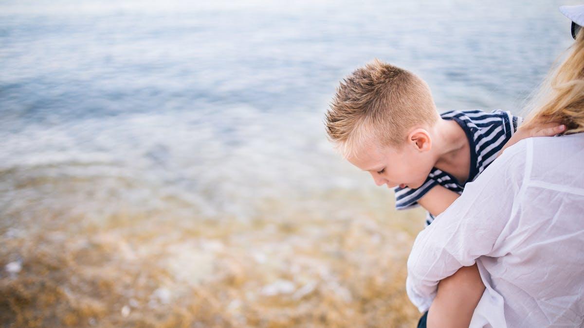 enfant dans les bras de sa maman au bord de l'eau