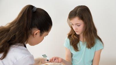 petite fille faisant vérifier  sa glycémie
