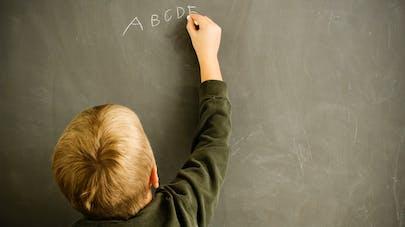 enfant écrit des lettres