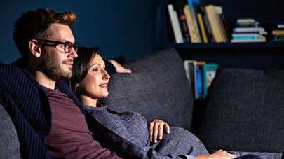 femme enceinte et son mari devant tv