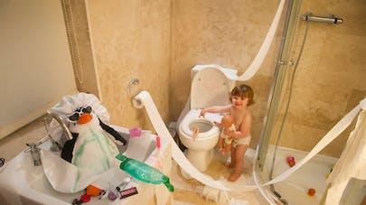 un enfant déroule du papier WC