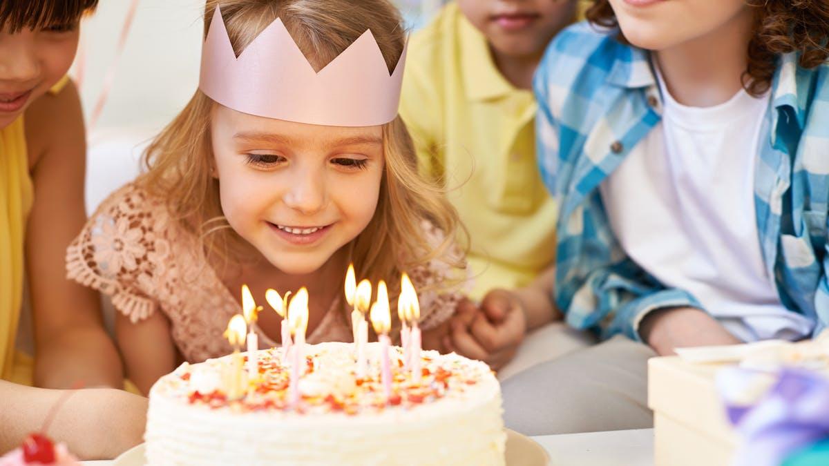fillette soufflant ses bougies d'anniversaire