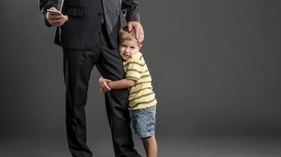 enfant accroché à la jambe de son père