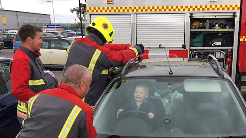 Un petit garçon coincé dans une voiture passe un bon moment avec les pompiers