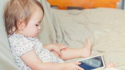bébé sur canapé jouant à la tablette