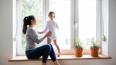 enfant à la fenêtre tenu par sa maman
