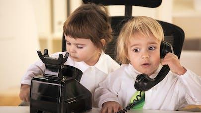 deux enfants avec un téléphone à l'ancienne