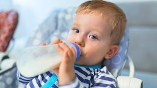grand bébé avec un biberon de lait