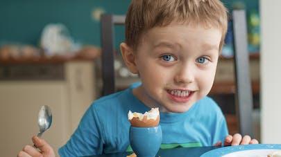 enfant mange un oeuf