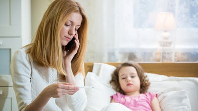 fillette couchée et mère prenant sa température