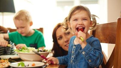 famille à table enfant croque tomate