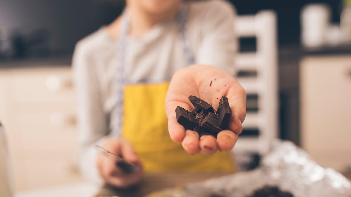 petite fille montre carrés chocolat