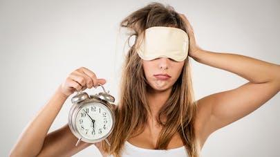 femme avant bandeau sur les yeux et réveil dans la main