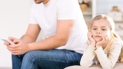Père au téléphone portable et sa fille s'ennuyant