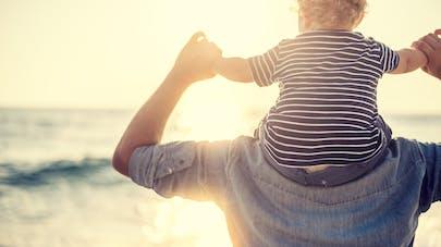 bébé sur le dos de son père