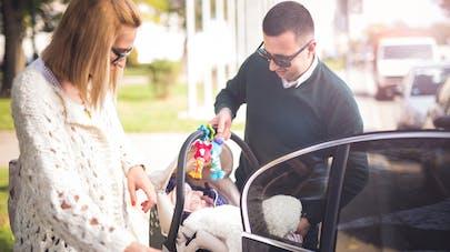 couple avec jeune bébé entrent dans une voiture