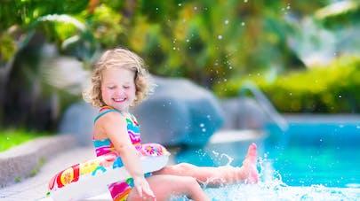Petite fille avec bouée autour de la taille au bord de la piscine