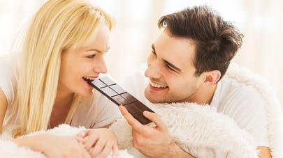 Couple au lit croquant une tablette de chocolat