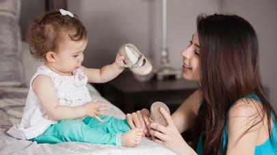 maman mettant des chaussures à son bébé