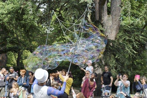 Un artiste fait de grosses bulles en plein air