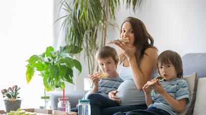femme enceinte et ses garçons mangeant une pizza