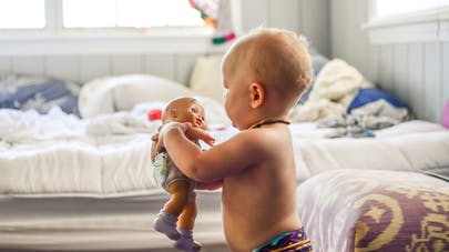 Bébé tenant une poupée dans ses  bras