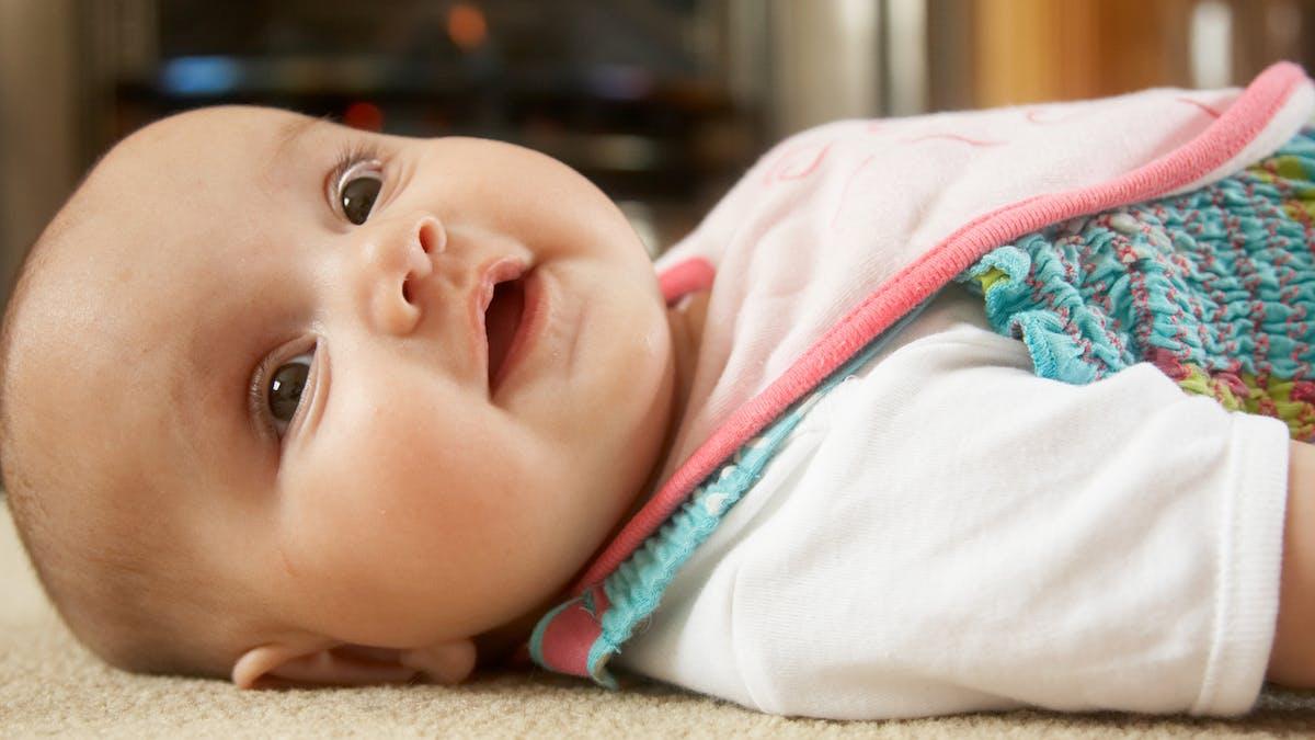bébé allongé sur un tapis
