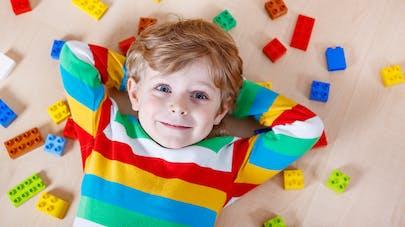 un enfant au milieu de Legos en couleurs