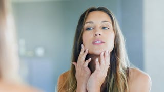 femme inspecte sa peau