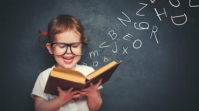 filette lisant un livre au tableau