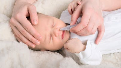 maman mettant du sérum physiologique dans le nez de bébé