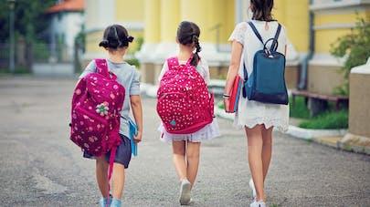 3 fillettes de dos sur le chemin de l'école