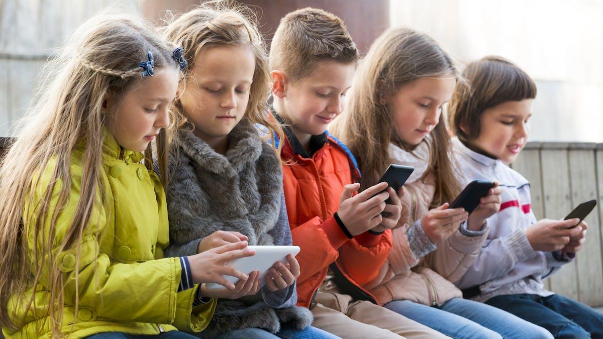 enfants jouant sur tablette et teléphone portable