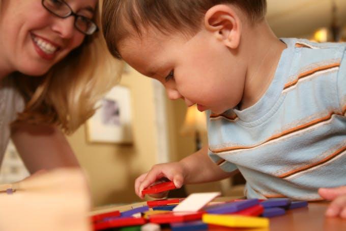 enfant fait un jeu Montessori avec sa mère