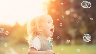 enfant souffle dans des bulles de savon