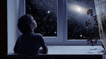 enfant regardant les étoiles par la fenêtre de sa chambre