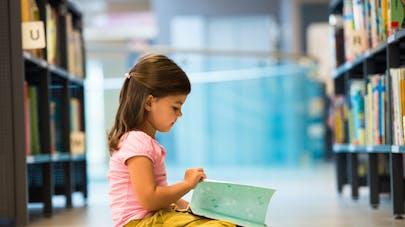 petite fille dans une bibliothèque-