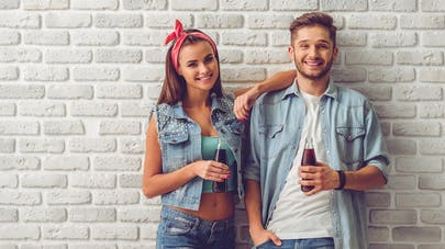 2  adolescents buvant un soda