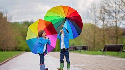 deux enfants jouent avec des parapluies dans un parc