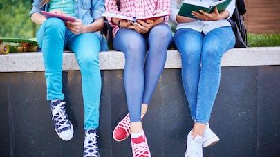 trois filles en pantalon assises sur un mur