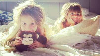 deux fillettes  éveillées dans le lit