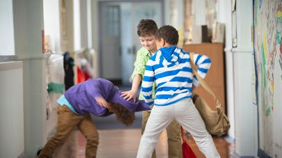 3 enfants se battant dans les couloirs de l'école