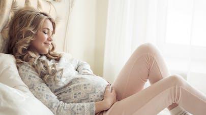 femme enceinte assise sur son lit