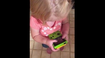 Une petite fille tente de comprendre comment fonctionne une Game Boy