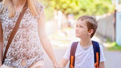 un enfant sur le chemin de l'école avec sa mère