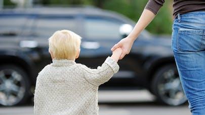 enfant donnant la main à sa mère en traversant la rue