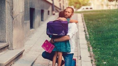 petite fille dans les bras de son père avant départ à l'école.